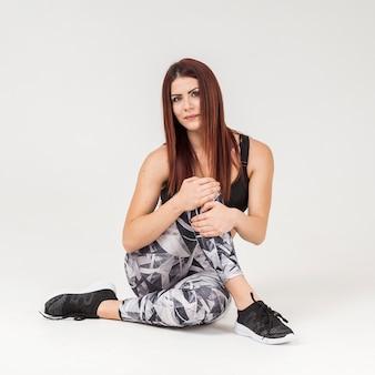 Vista frontale della donna sportiva che posa mentre indossando l'abbigliamento di allenamento