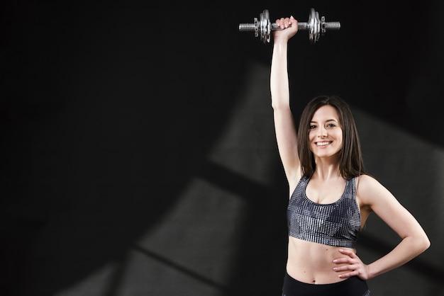 Vista frontale della donna sportiva con manubri