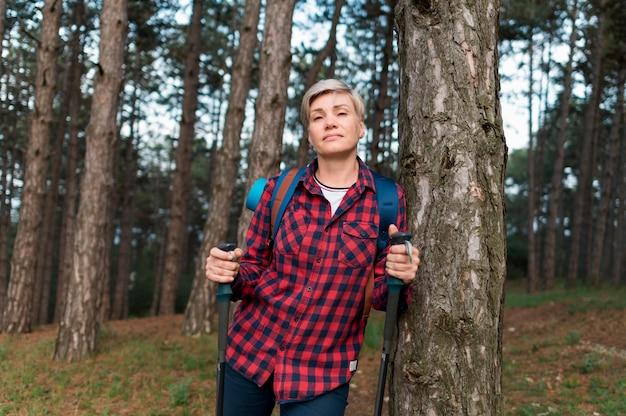 Vista frontale della donna turistica più anziana che posa nella foresta