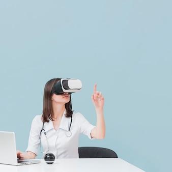 Vista frontale della dottoressa utilizzando le cuffie da realtà virtuale