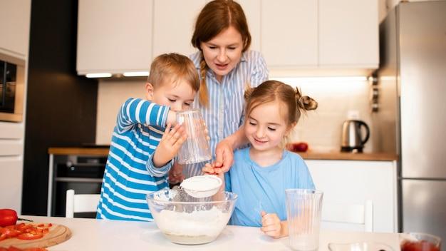 Vista frontale della famiglia che cucina a casa