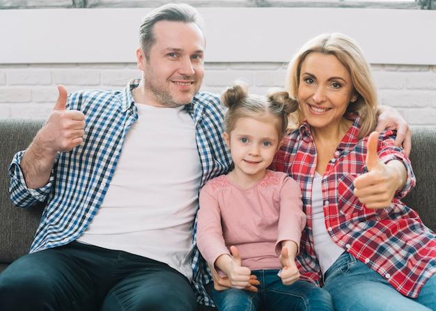 Vista frontale della famiglia felice che mostra pollice sul segno che si siede sul divano