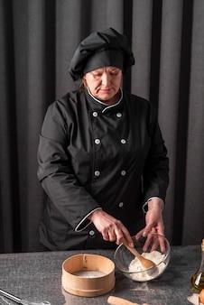 Vista frontale della farina di setacciatura del cuoco unico femminile