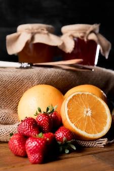 Vista frontale della frutta con vasetti di marmellata