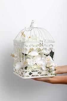 Vista frontale della gabbia per uccelli tenuta in mano con i fiori
