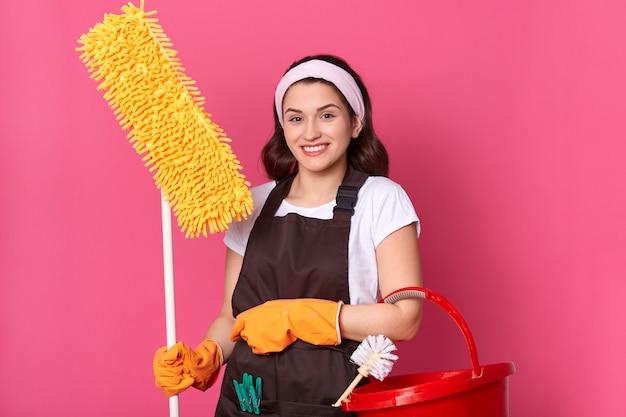 Vista frontale della giovane casalinga sorridente in abiti casual e grembiule