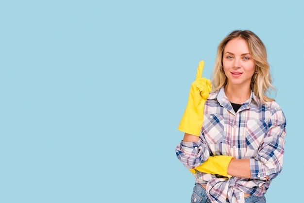 Vista frontale della giovane donna che punta verso l'alto guardando la telecamera su sfondo blu
