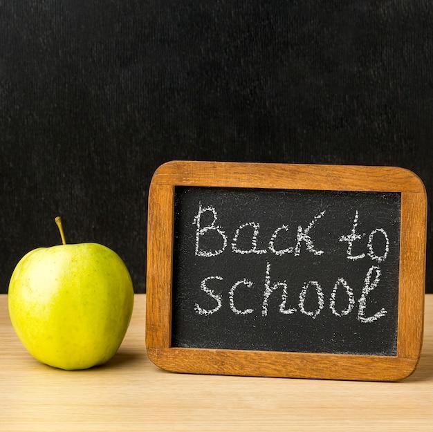 Vista frontale della lavagna con la mela per di nuovo a scuola