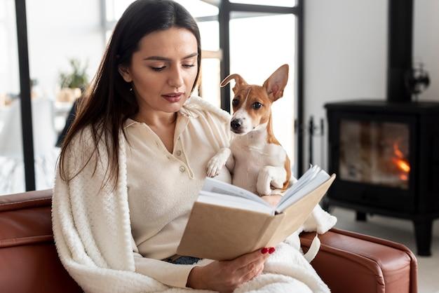 Vista frontale della lettura della donna mentre si tiene il suo cane
