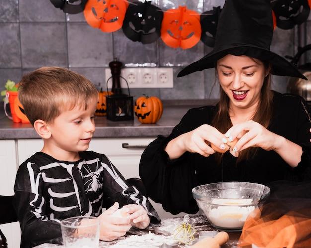 Vista frontale della madre e del figlio che producono i biscotti