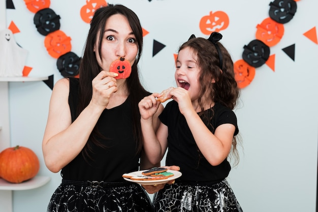 Vista frontale della madre e della figlia che mangiano i biscotti