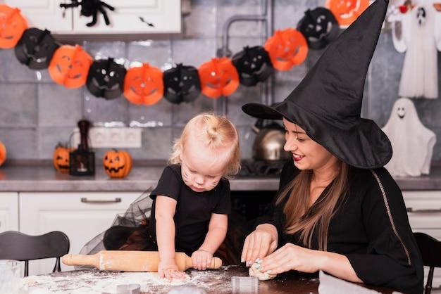 Vista frontale della madre e della figlia che producono i biscotti