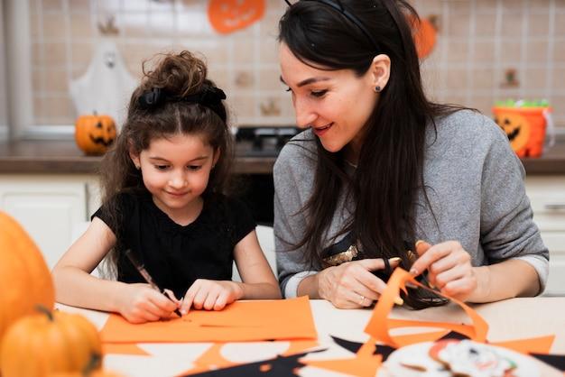 Vista frontale della madre e della figlia in cucina