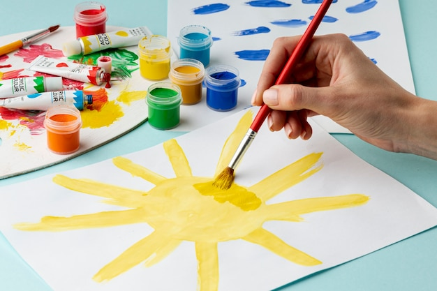 Vista frontale della mano che dipinge un sole