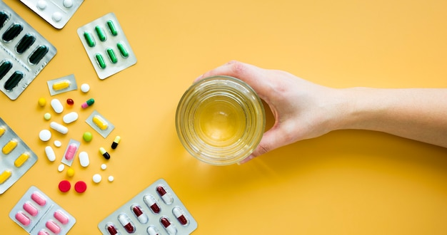 Vista frontale della mano che tiene bicchiere d'acqua con le pillole e le stagnola