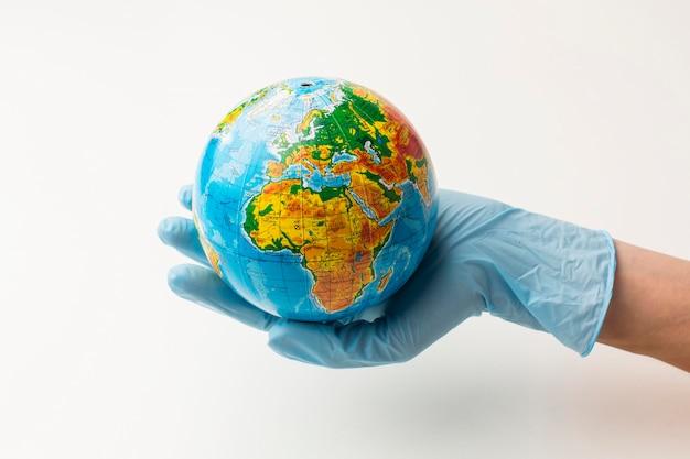 Vista frontale della mano con i guanti che tengono il globo della terra