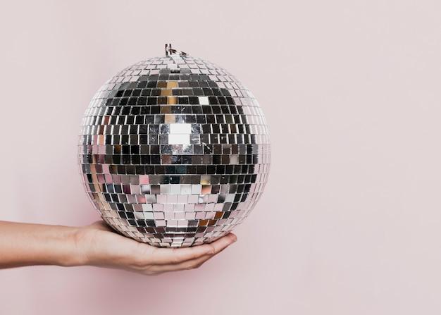 Vista frontale della palla da discoteca tenuta in mano