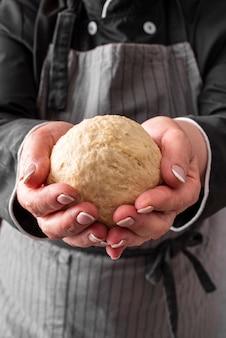 Vista frontale della palla di pasta tenuta dal cuoco unico femminile