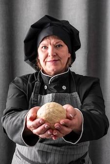 Vista frontale della palla femminile della pasta della tenuta del cuoco unico