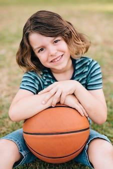 Vista frontale della pallacanestro della tenuta del ragazzo