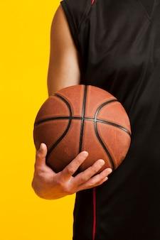 Vista frontale della pallacanestro tenuta in una mano dal giocatore maschio