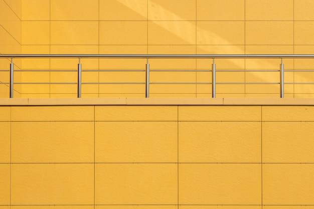 Vista frontale della parete piastrellata di colore giallo caldo con balaustra in metallo