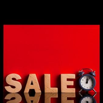 Vista frontale della parola e dell'orologio di vendita su fondo rosso e nero