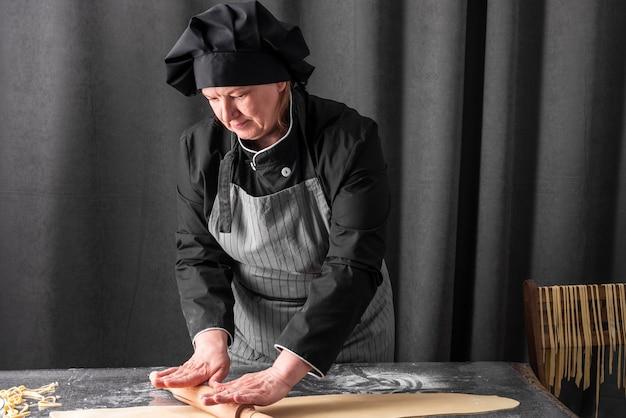 Vista frontale della pasta di rotolamento del cuoco unico femminile