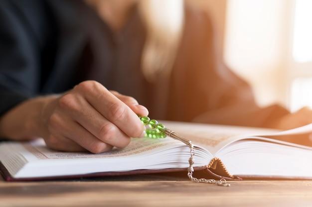 Vista frontale della persona che legge dal libro sacro
