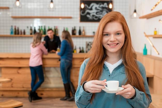 Vista frontale della ragazza carina con caffè
