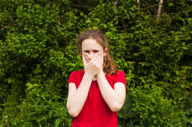 Vista frontale della ragazza che esamina macchina fotografica che copre la sua bocca del parco