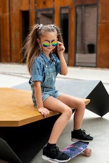 Vista frontale della ragazza con skateboard e occhiali da sole