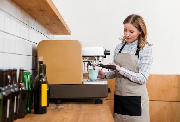 Vista frontale della ragazza di barista che produce caffè