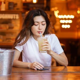 Vista frontale della ragazza giapponese carina che beve limonata