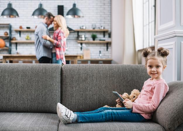 Vista frontale della ragazza sorridente che tiene compressa digitale con i suoi genitori vaghi nella priorità bassa