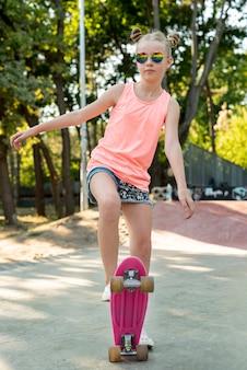 Vista frontale della ragazza su skateboard rosa