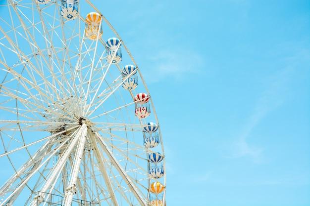 Vista frontale della ruota di ferris variopinta a metà retrò al parco di divertimenti sopra il fondo del cielo blu