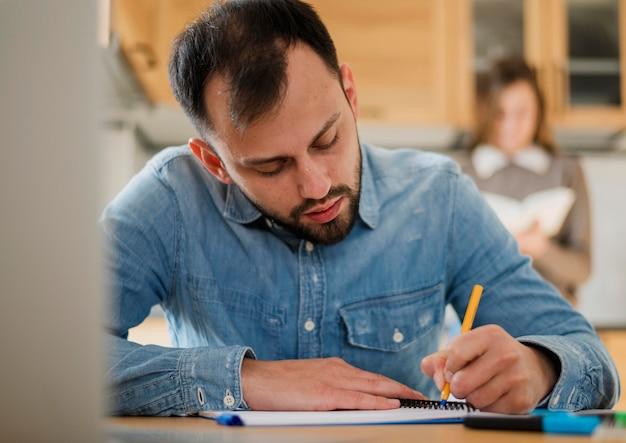 Vista frontale della scrittura dell'uomo sul taccuino allo scrittorio