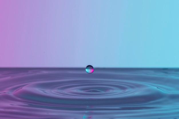 Vista frontale della spruzzata di liquido dalla goccia trasparente