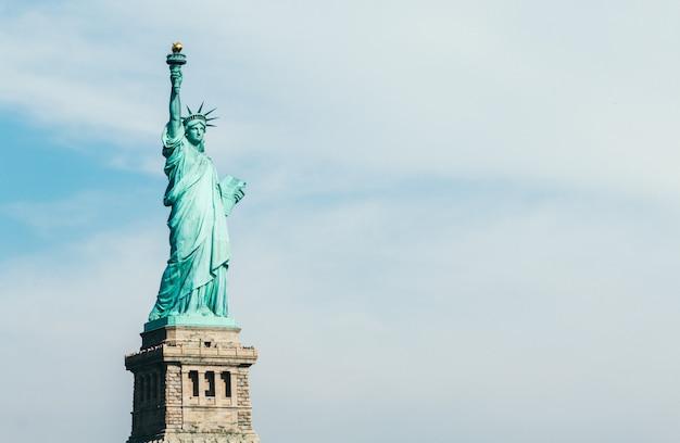 Vista frontale della statua della libertà a new york con cielo blu e copia spazio per il testo