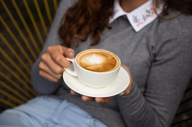 Vista frontale della tazza di caffè della holding della donna