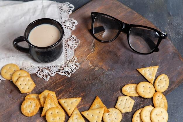 Vista frontale della tazza di latte con gli occhiali da sole e le patatine fritte sullo scrittorio di legno e sulla superficie grigia