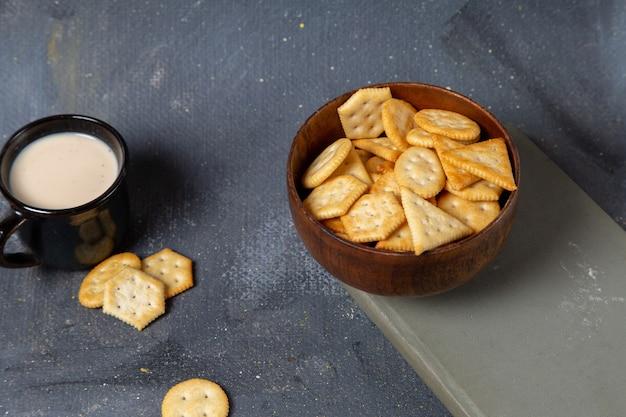 Vista frontale della tazza di latte con piastra marrone pieno di cracker sulla superficie grigia