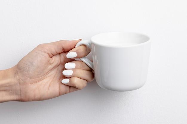 Vista frontale della tazza di latte tenuta in mano