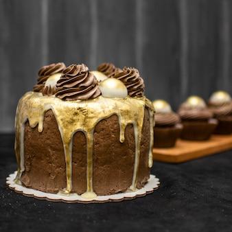 Vista frontale della torta al cioccolato con cupcakes sfocati