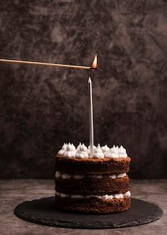 Vista frontale della torta sull'ardesia con la candela
