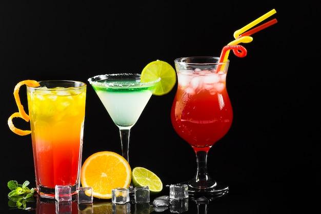 Vista frontale della varietà di cocktail con cannucce e cubetti di ghiaccio