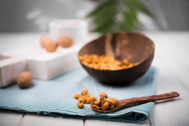 Vista frontale delle arachidi in cucchiaio e panno