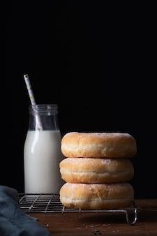 Vista frontale delle ciambelle impilate con lo spazio della copia e della bottiglia per il latte