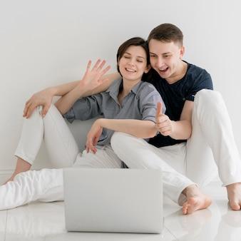 Vista frontale delle coppie adorabili a casa